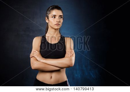 Young beautiful sportive girl posing with crossed arms over dark background. Copy space.
