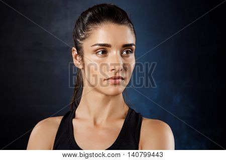 Portrait of young beautiful brunette  sportive girl posing over dark background. Copy space.