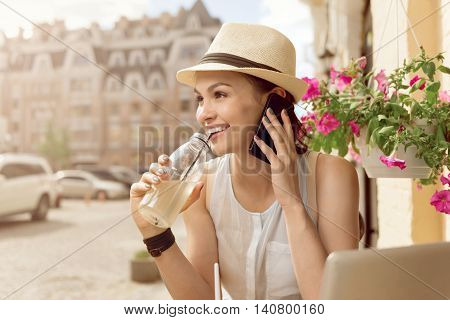 My lifestyle. Cheerful beautiful content woman drinking lemonade and talking on cellphone while standing outside the cafe