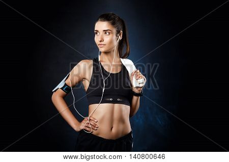 Young beautiful brunette sportive girl listening music over dark background. Copy space.