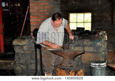 Lancaster Pennsylvania - October 14 2015: Blacksmith working on an iron anvil at the Landis Valley Village and Farm Museum blacksmith shop