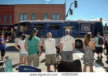 KALISPELL, MT, USA - JULY 4 : Campaign bus of US Representative Ryan Zinke (R-MT) drives in 4th of July Parade on Main Street in Kalispell, Montana, on July 4, 2016, as a crowd of spectators watches.