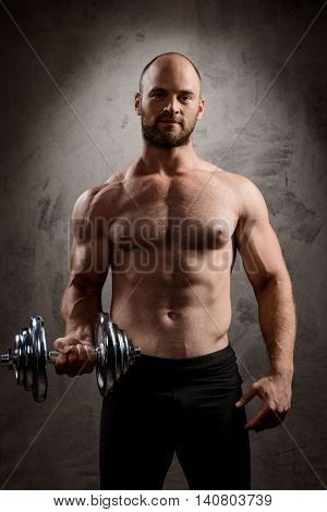 Young powerful sportsman training with dumbbells, looking at camera over dark background.