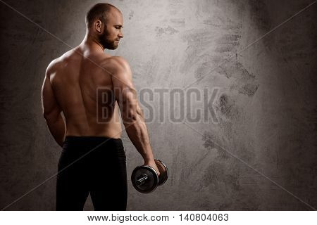 Young powerful sportsman training with dumbbells, standing back to camera over dark background. Copy space.