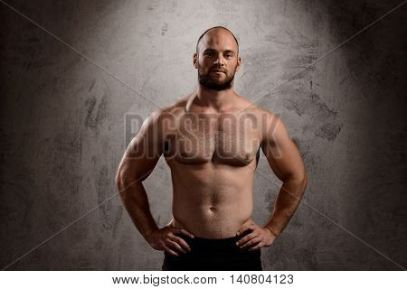 Portrait of young powerful sportsman looking at camera over dark background. Copy space.