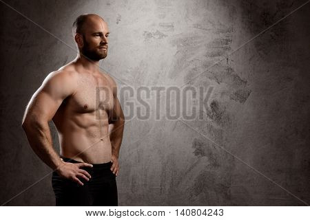 Portrait of young powerful sportsman standing over dark background. Copy space.