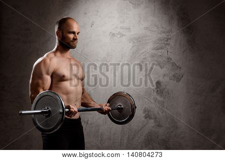 Young powerful sportsman training with barbell over dark background. Copy space.