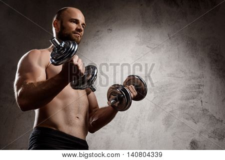 Young powerful sportsman training with dumbbells over dark background. Copy space.