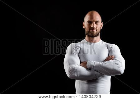 Young powerful sportsman in white clothing looking at camera, smiling, arms crossed over black background. Copy space.