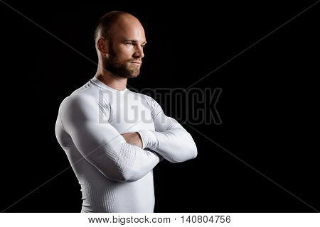 Young powerful sportsman in white clothing, arms crossed, over black background. Copy space.