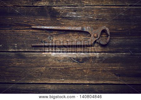 old rusty tongs on wooden boards background