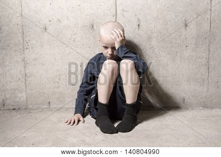 A Neglected lonely child leaning at the wall