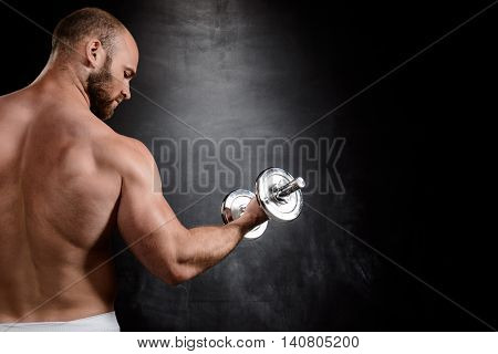 Close up photo of young powerful sportsman training with dumbbells, standing back to camera over black background.