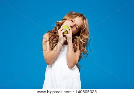 Young pretty girl eating green apple, looking at camera over blue background. Copy space.