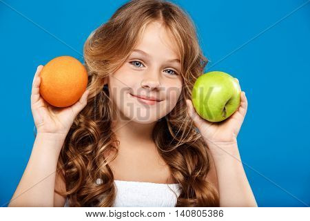 Young pretty girl holding apple and orange, smiling, looking at camera over blue background. Copy space.