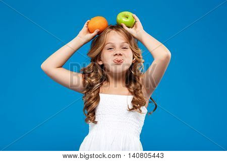Young pretty girl holding apple and orange above head, showing tongue, looking at camera over blue background. Copy space.