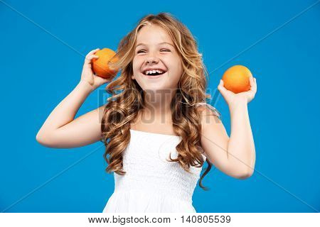 Young pretty girl holding oranges, smiling over blue background. Copy space.