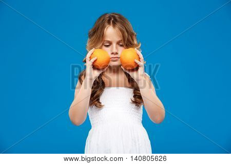 Young pretty girl holding oranges over blue background. Copy space.