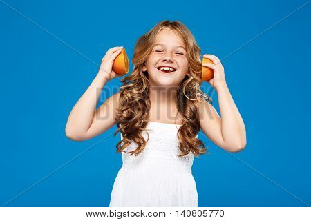 Young pretty girl holding oranges, smiling, eyes closed over blue background. Copy space.
