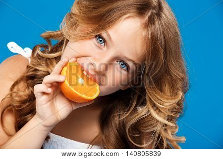 Young pretty girl eating orange, looking at camera over blue background. Close up. Copy space.