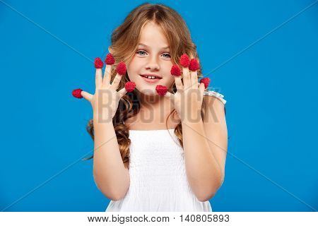 Young pretty girl holding raspberry, looking at camera, smiling over blue background. Copy space.