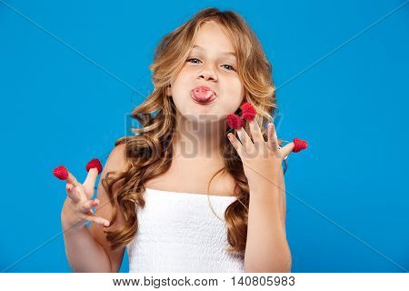 Young pretty girl eating raspberry, looking at camera, showing tongue over blue background. Copy space.