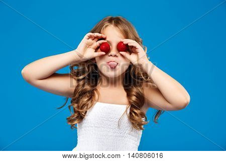 Young pretty girl hiding eyes with strawberry, showing tongue over blue background. Copy space.