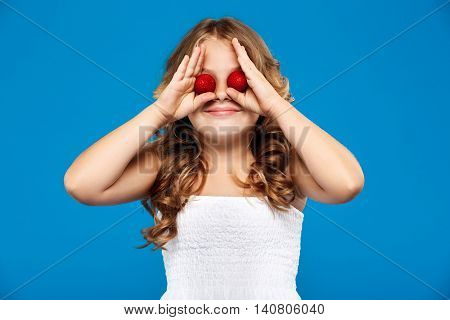 Young pretty girl hiding eyes with strawberry, smiling over blue background. Copy space.