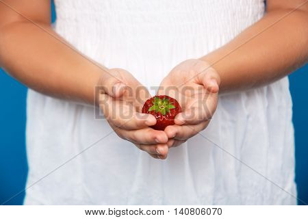 Close up photo of girl's hand holding strawberry over blue background.