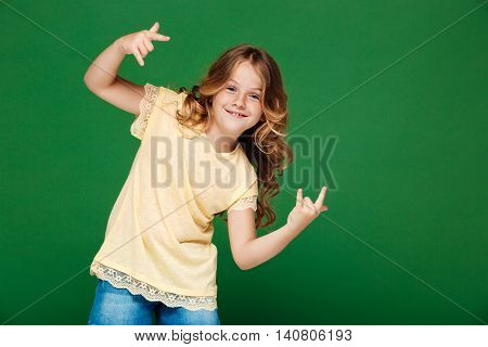 Young pretty girl smiling, looking at camera over green background. Copy space.