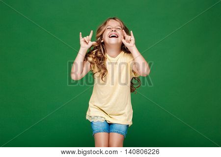 Young pretty girl laughing over green background. Copy space.