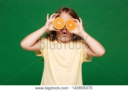 Young pretty girl hiding eyes with oranges, mouth opened over green background. Copy space.