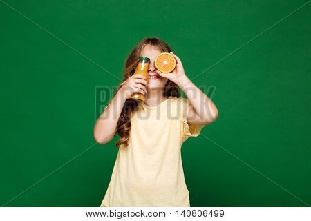 Young pretty girl hiding eyes with orange and juice, smiling over green background. Copy space.