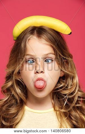 Young pretty girl holding banana on head, showing tongue, fooling over pink background.