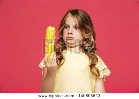 Young pretty girl holding corn,  over pink background. Copy space.