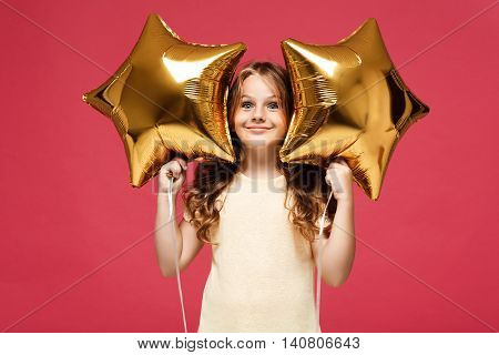 Young pretty girl holding balloons, looking at camera and smiling over pink background.