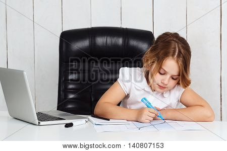 Young beautiful girl drawing graph, sitting at working place in office.