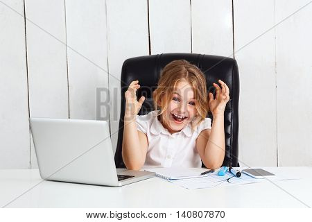 Young beautiful girl sitting at working place, looking to camera, laughing in office.