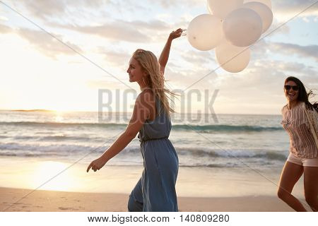 Two Women Running On The Beach With Balloons