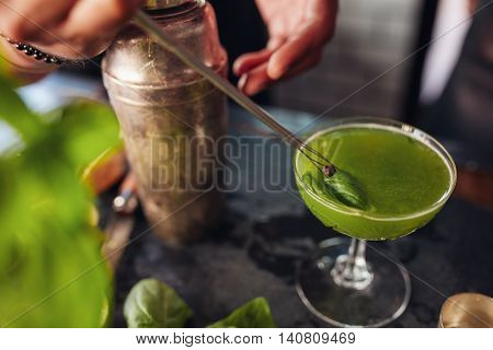 Barman Hands Garnishing Fresh Green Cocktail