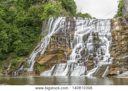 Ithaca Falls a waterfall in New York's Finger Lakes Region cascades down a tall rocky cliff.