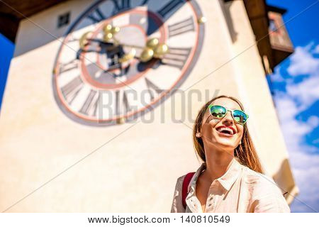 Young smiling woman in front of the old clock tower in Graz town. Traveling in Austria