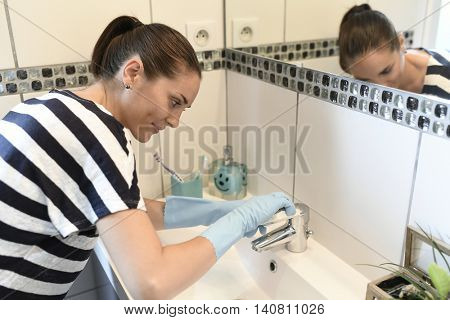 young woman cleaning bathroom faucet