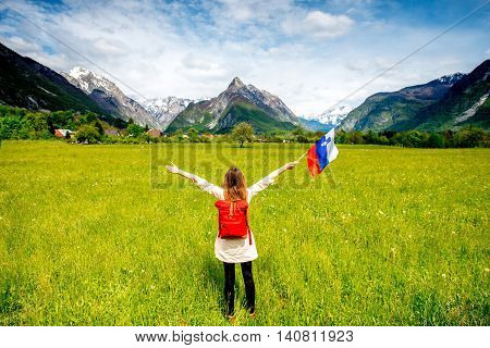 Beautiful landscape with mountains, green field and woman holding slovenian flag. Traveling in Triglav national park in Slovenia