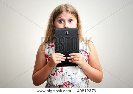 Little girl smiling and surprised with tablet computer