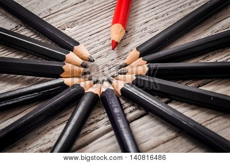 Red pencil stands out from the crowd of black pencil on a wooden white background. Leadership, uniqueness, independence, initiative, strategy, disagree, think, different, concept of business success