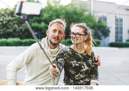 Young happy couple making photo using selfie stick outdoors