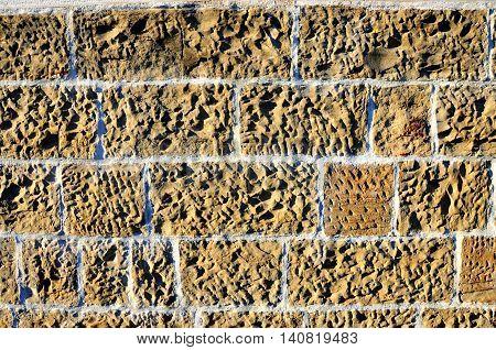 An ecru or camel, umber brickwall texture