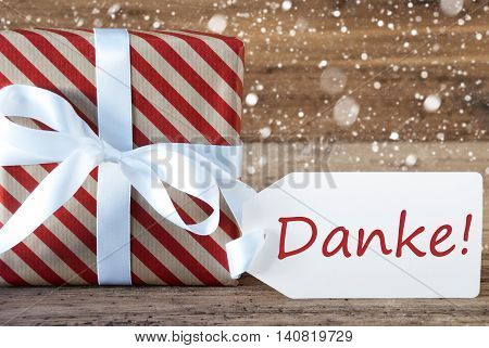Christmas Gift Or Present On Wooden Background With Snowflakes. Card For Seasons Greetings. White Ribbon With Bow. German Text Danke Means Thank You