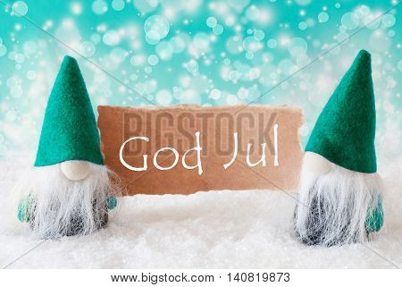 Christmas Greeting Card With Two Turqoise Gnomes. Sparkling Bokeh Background With Snow. Swedish Text God Jul Means Merry Christmas